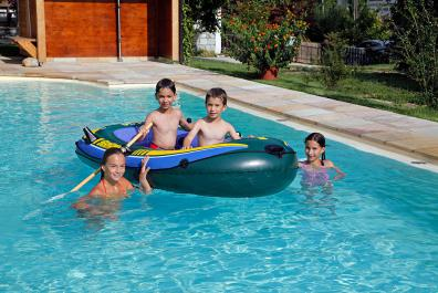 Children playing with rubber dinghy in the pool